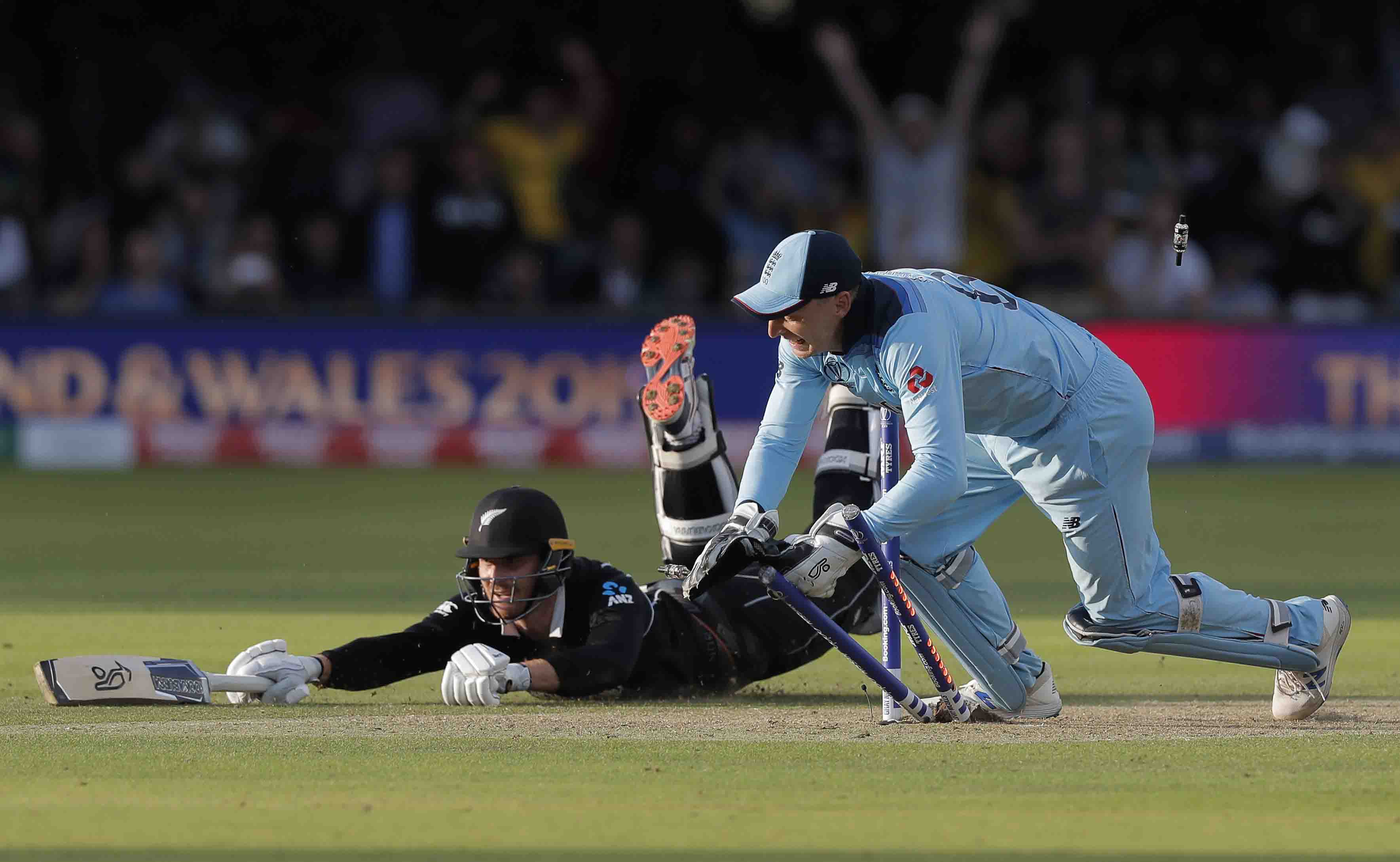 England wicketkeeper Jos Buttler runs out New Zealand's Martin Guptill off the last ball of the Super Over to secure victory for England at the ICC Men's Cricket World Cup Final at Lord's.
