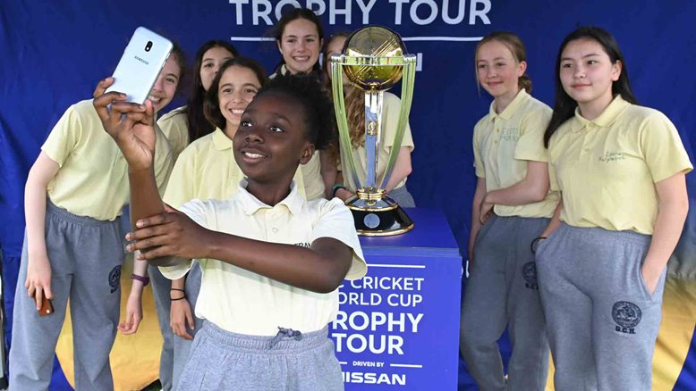 Local school children pose with the World Cup trophy.