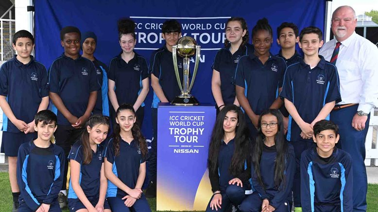 Mike Gatting and local school children pose with the World Cup trophy.